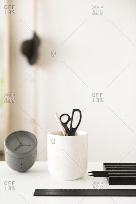 Clock, pencil cup, and accessories on desk