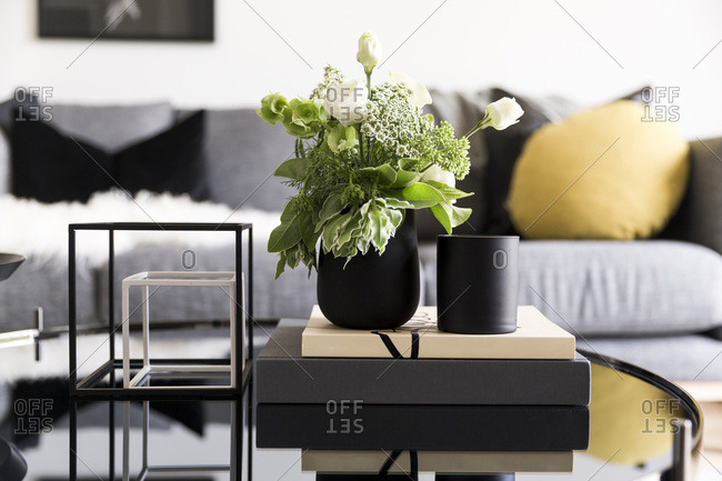 Green and white flower arrangement on coffee table in modern living room