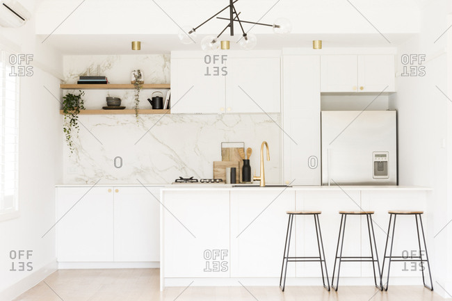 Stools at counter in modern white kitchen