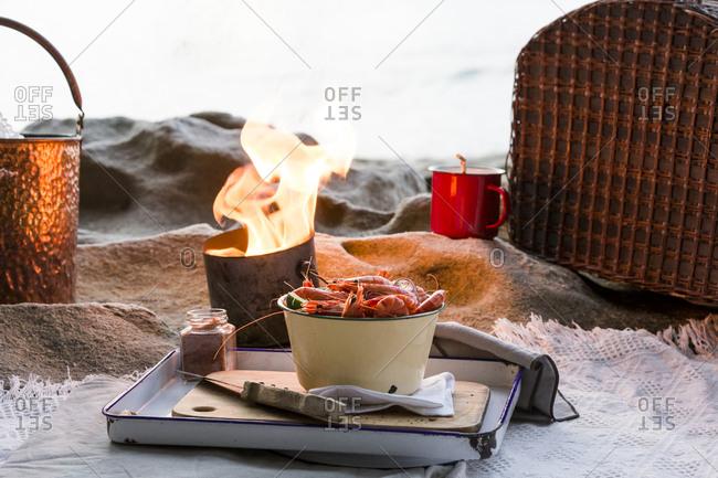 Pot of shrimp by firelight on beach