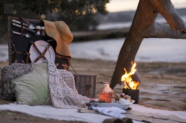 Picnic basket on beach by firelight