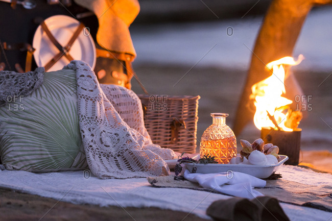 Romantic picnic on the beach with campfire