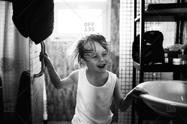 Boy shaking wet hair in bathroom