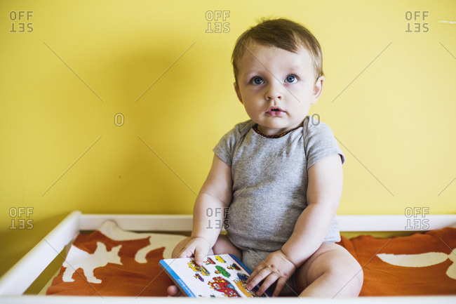 Toddler boy on changing table with book