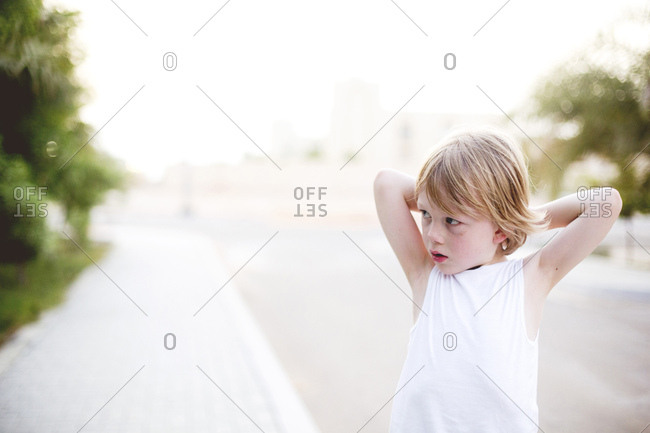 Blonde boy staring away standing outside