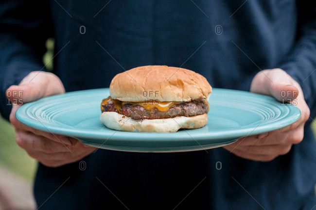Man holding blue plate with a cheeseburger