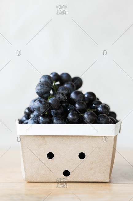 Concord grapes in a container on a white background