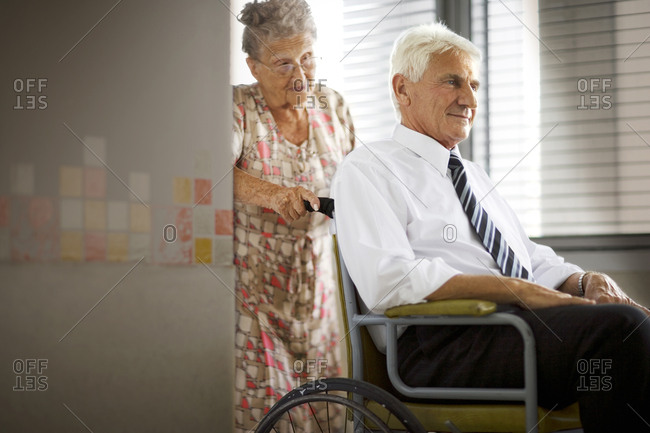 Senior woman pushing her husband in a wheelchair