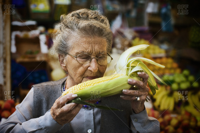Senior woman inspecting an ear of corn at the grocer's