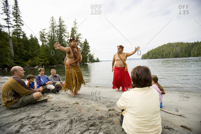 Family being entertained by traditional pacific island dancers on the beach