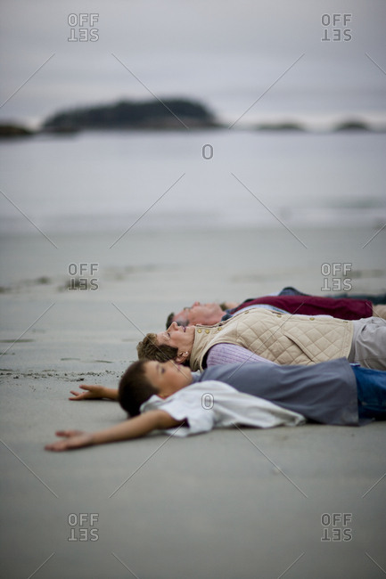 Grandparents and their grandson lying down on the beach