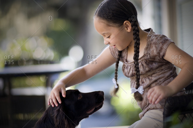 Young girl petting her dog