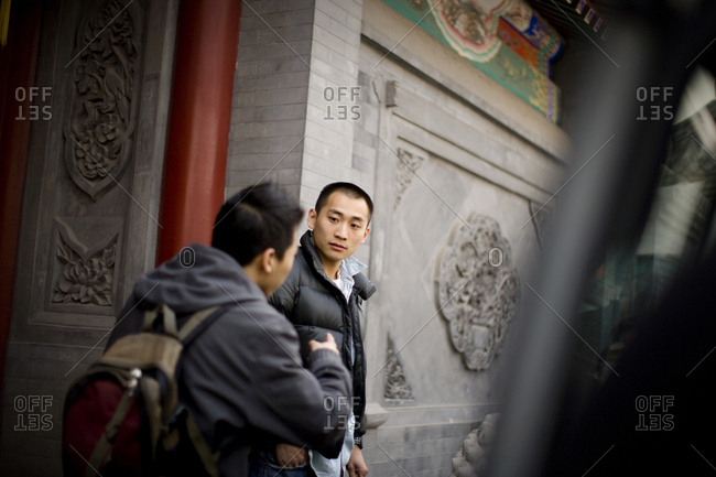 Two young men outside a carved building facade