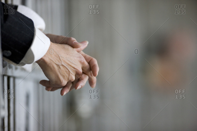 Hands of a businessperson clasped through the bars of a prison cell