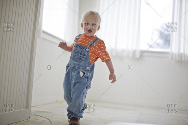 Toddler boy wearing denim overalls
