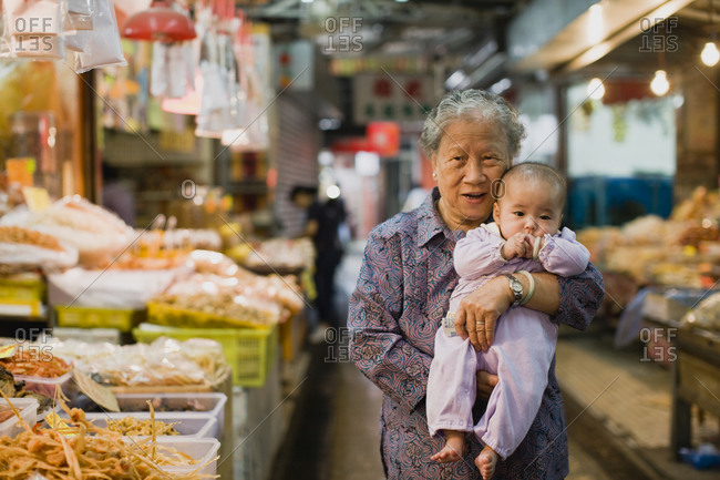 Grandmother holding her baby grandchild at a market