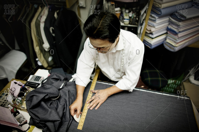 Tailor measuring fabric in his workshop