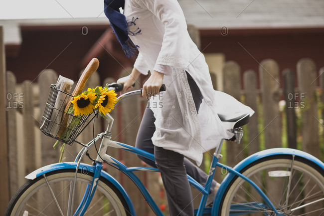 Woman cycling with sunflowers and a baguette in her bike basket
