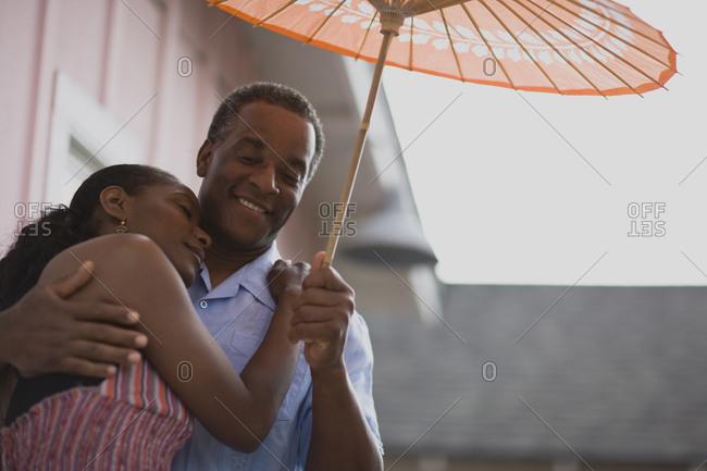 Couple hugging underneath a parasol