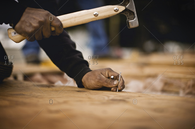 Carpenter hammering a nail into place