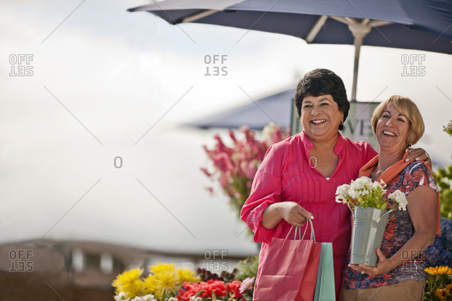 Two friends buying flowers at a market