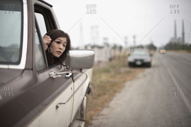 Young woman applying mascara using her wing mirror