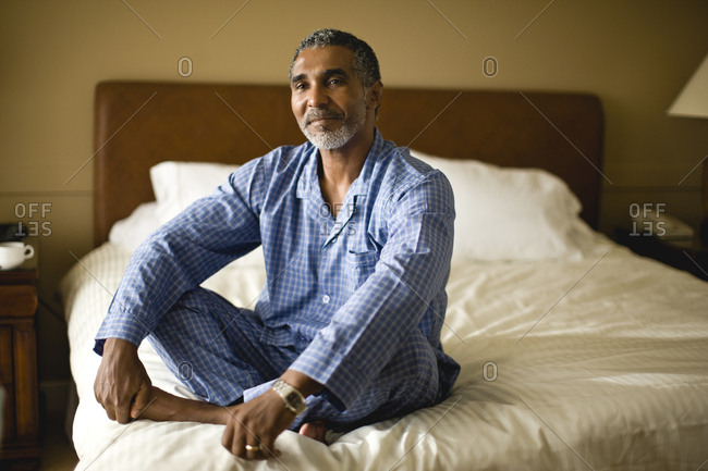 Man sitting on his bed in his pajamas