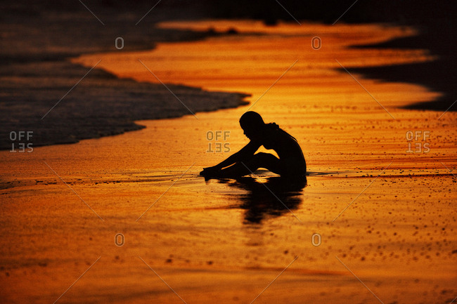 Woman silhouetted on the beach at sunset
