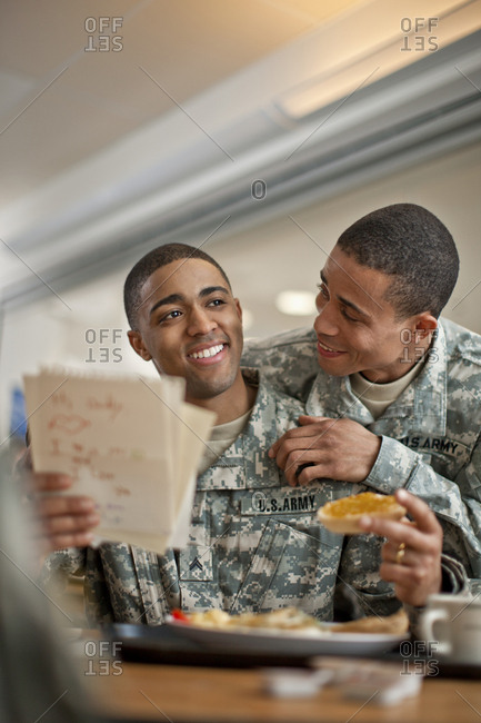 Soldier's laughing while eating in the canteen