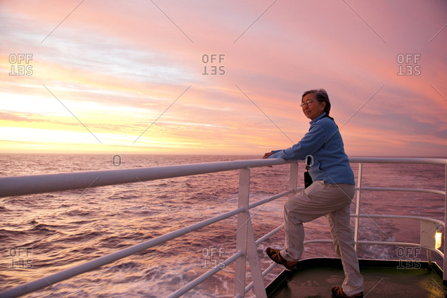 Woman admiring the sunset from a boat deck