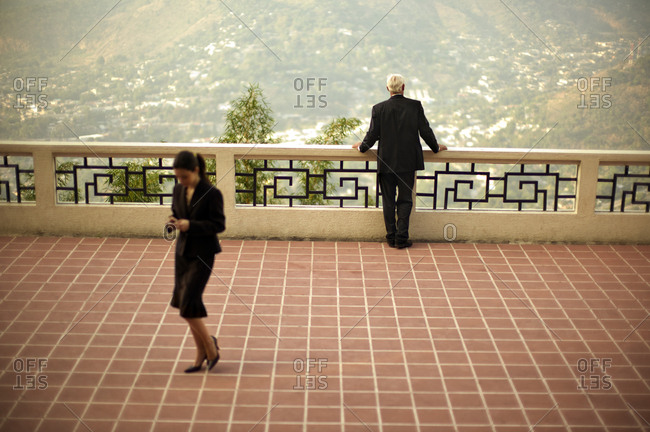 Businessman and businesswoman on a balcony with a scenic look out