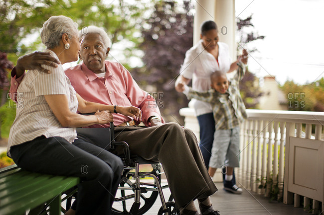 Elderly couple spending time with family on their porch