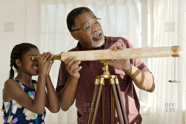 Grandfather and granddaughter using a telescope
