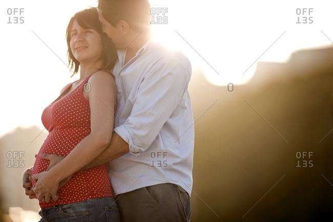 Man embracing his pregnant partner