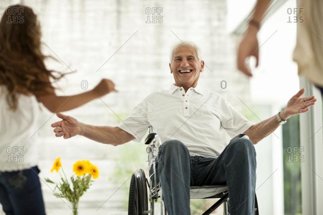 Senior man in a wheelchair greeting family members