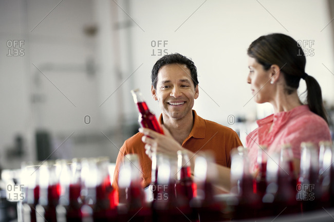 Workers examining bottles on a production line