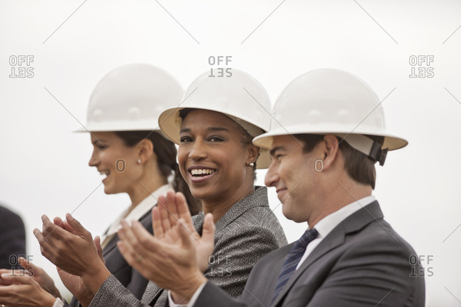 Business colleagues in hard hats applauding
