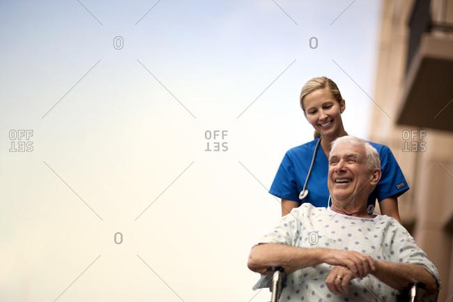 Nurse pushing an elderly patient in a wheelchair