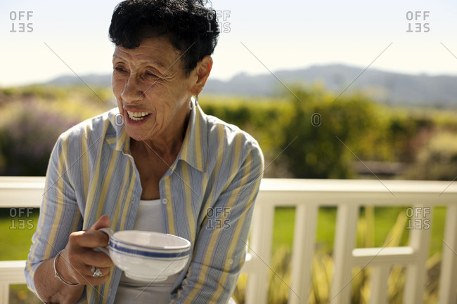 Woman enjoying a cup of coffee on her veranda