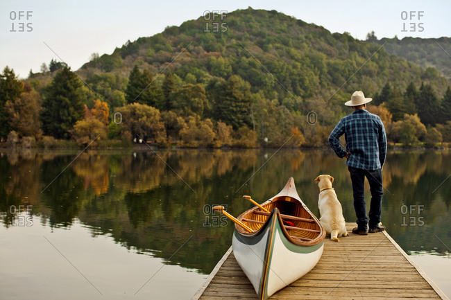 Man looking out at a tranquil lake with his dog