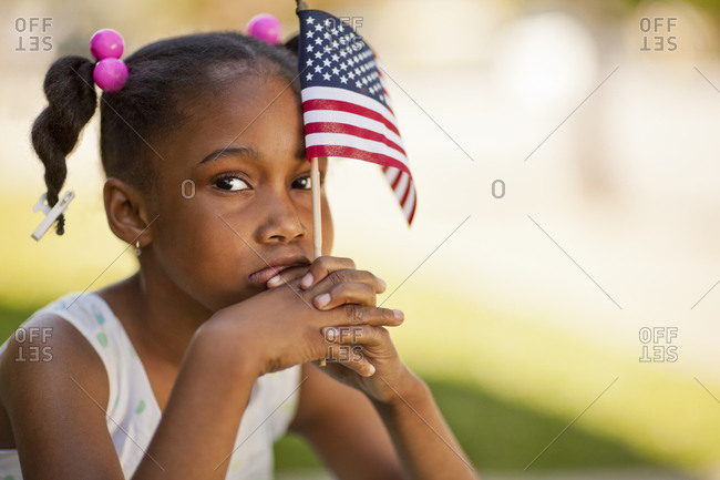 Young girl holding a miniature American flag