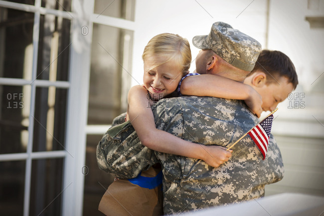 Returned soldier hugging his two children