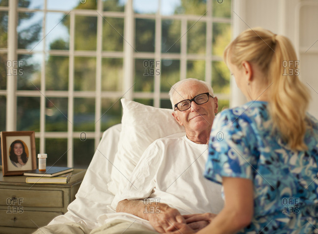 Ill senior man receiving a visit from a family member