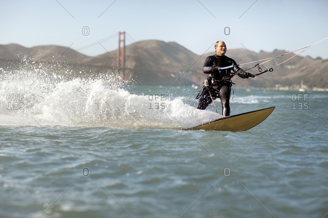 Kite boarder riding with the Golden Gate Bridge in the background, San Francisco, California, USA