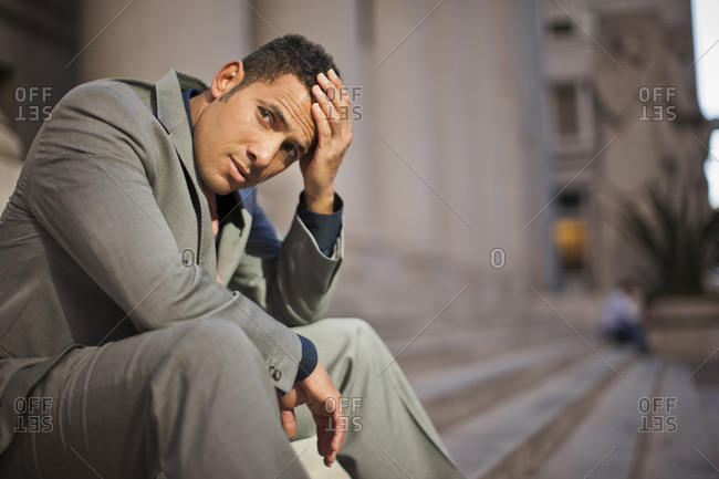 Businessman sitting on the steps outside a building