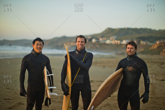 Three surfers on the beach