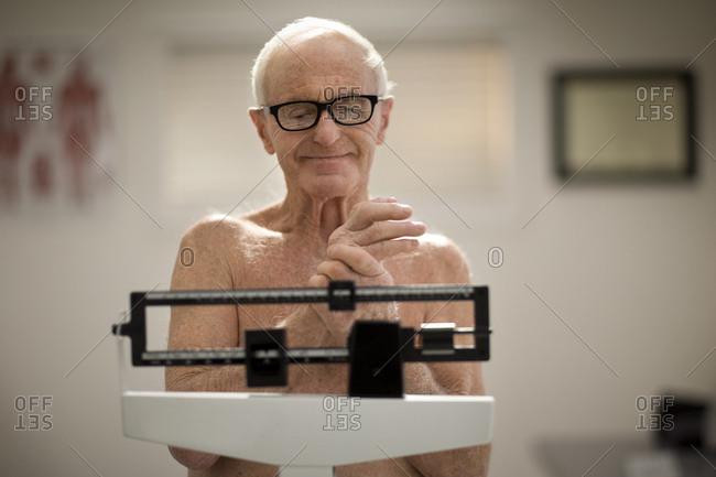 Senior man being weighed