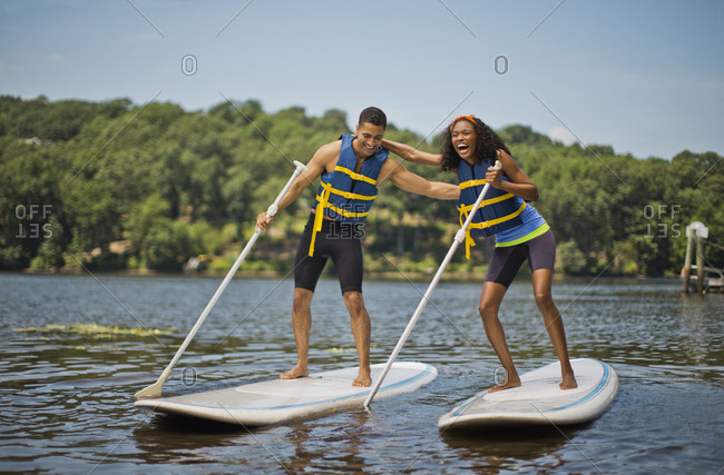 Young couple paddle boarding together