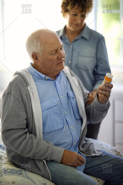Senior couple examining a pill bottle