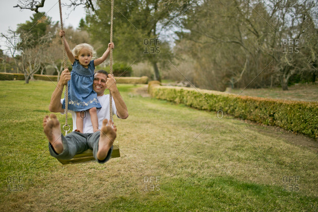 Father and daughter swinging on a tree swing